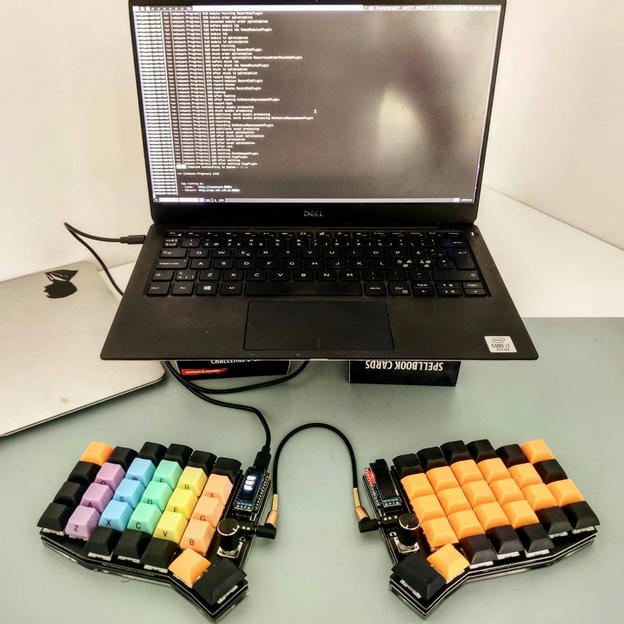 Laptop from 45deg with external Sofle split keyboard and colorful keys